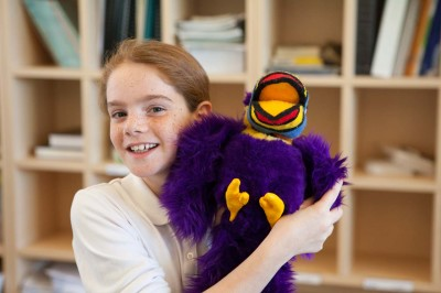 Smiling girl with toucan doll